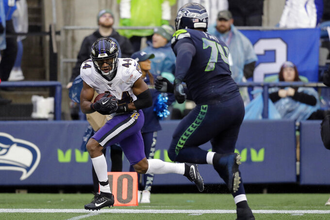 Baltimore Ravens cornerback Marlon Humphrey (44) runs for a touchdown after recovering a Seattle Seahawks fumble as Seahawks offensive tackle George Fant, right, pursues, during the second half of an NFL football game, Sunday, Oct. 20, 2019, in Seattle. (AP Photo/John Froschauer)