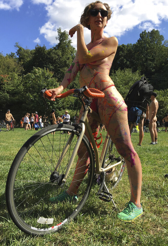 EDS NOTE: NUDITY - FILE - In this Sept. 9, 2017, file photo Olivia Neely, a topless cyclist wearing body paint, motions before the start of that year's annual Philly Naked Bike Ride in Philadelphia. Organizers of the Philly Naked Bike Ride say this year's event will take place Aug. 28, 2021, after last year's event was cancelled due to COVID-19, but masks will be required, even if pants and shirts are not. (AP Photo/Dino Hazell, File)
