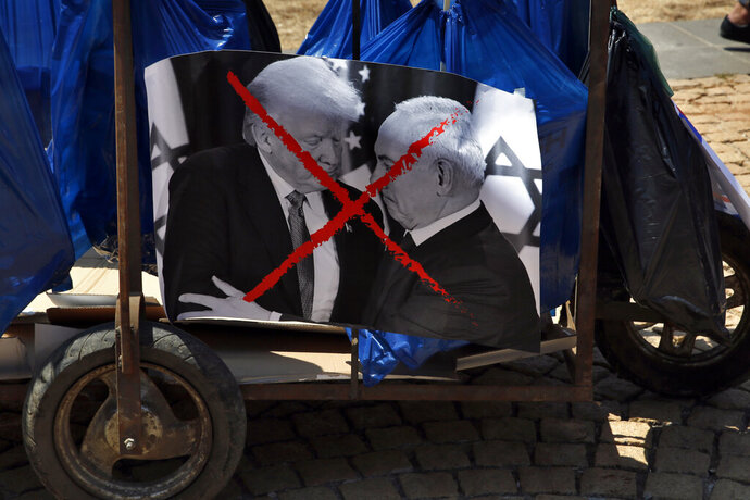 A trash trolly decorated with a photo of U.S. President Donald Trump and Israeli Prime Minister Benjamin Netanyahu during a demonstration organized by the Islamic militant group Hamas against a U.S.-sponsored Middle East economic workshop in Bahrain, in front of the United Nations headquarters in Beirut, Lebanon, Tuesday, June 25, 2019. The Trump administration is plowing ahead with a $50 billion economic proposal to aid the Palestinians and hopes it'll drive a much-anticipated but unseen Mideast peace plan. The two—day workshop is to begin Tuesday, where the Trump administration's Mideast peace team hopes to drum up regional support and secure financial pledges from Arab and Israeli stakeholders. (AP Photo/Bilal Hussein)