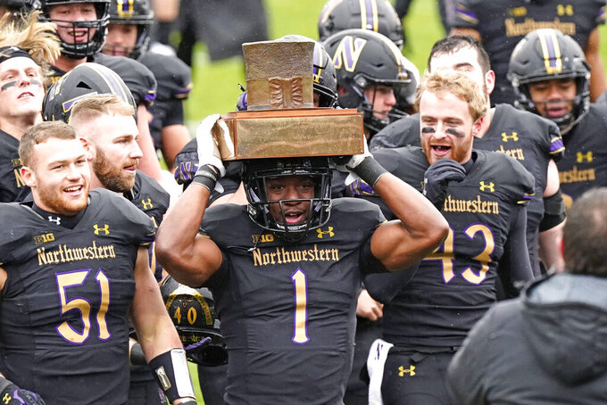 Northwestern running back Jesse Brown (1) celebrates with teammates as he holds the Land of Lincoln Trophy after Northwestern defeated Illinois 28-10 in an NCAA college football game in Evanston, Ill., Saturday, Dec. 12, 2020. (AP Photo/Nam Y. Huh)