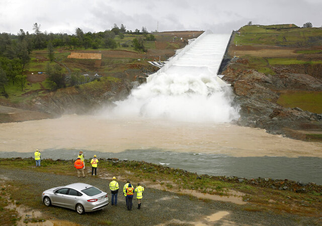 FILE - In this April 2, 2019, file photo, water flows down the Oroville Dam spillway in Oroville, Calif. In a rare reversal, the Trump administration has agreed to reimburse California for hundreds of millions of dollars in repair costs stemming from the 2017 emergency at Oroville Dam. (AP Photo/Rich Pedroncelli, File)