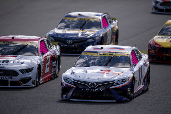 Denny Hamlin (11) leads a pack of cars during a NASCAR Cup Series auto racing race at Charlotte Motor Speedway, Sunday, Oct. 10, 2021, in Concord, N.C. (AP Photo/Matt Kelley)