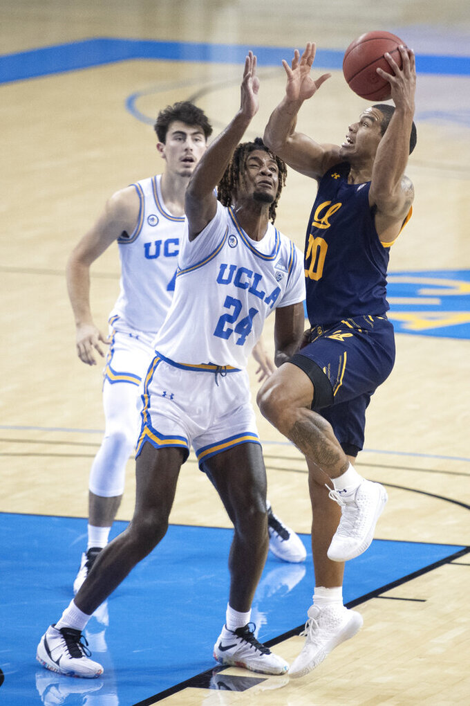 California guard Matt Bradley, right, goes up for a basket over UCLA forward Jalen Hill during the first half of an NCAA college basketball game Sunday, Dec. 6, 2020, in Los Angeles. (AP Photo/Kyusung Gong)