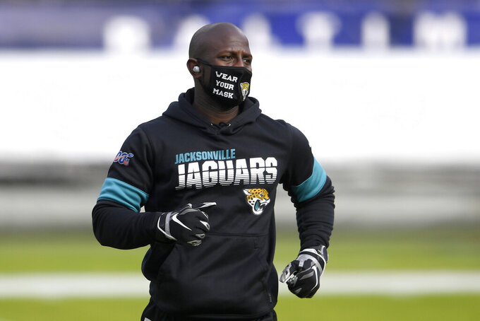Tim Owens, Jacksonville Jaguars player engagement and youth football manager, wears a face mask to protect against COVID-19 with a message while working out with players prior to an NFL football game against the Baltimore Ravens, Sunday, Dec. 20, 2020, in Baltimore. (AP Photo/Nick Wass)