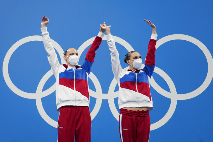 First placed Svetlana Kolesnichenko and Svetlana Romashina of Russian Olympic Committee celebrate during the medal ceremony of the duet free routine final at the the 2020 Summer Olympics, Wednesday, Aug. 4, 2021, in Tokyo, Japan. (AP Photo/Alessandra Tarantino)
