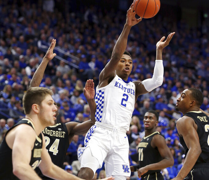 Kentucky's Ashton Hagans (2) passes between Vanderbilt's Matt Ryan, left, Aaron Nesmith (24), Simisola Shittu (11) and Joe Toye, right, during the second half of an NCAA college basketball game in Lexington, Ky., Saturday, Jan. 12, 2019. (AP Photo/James Crisp)