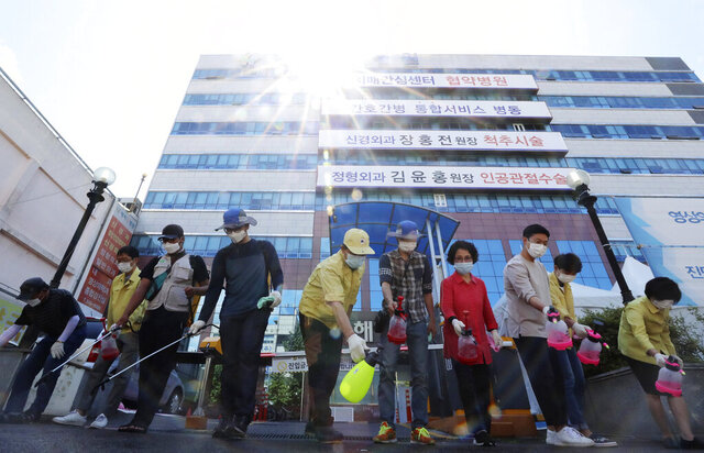 Health officials disinfect an area around a hospital after one of the hospital's patients tested positive for the new coronavirus in Gwangju, South Korea, Wednesday, July 1, 2020. South Korea is considering including religious facilities on the same list with nightclubs, hostess bars and karaoke rooms as