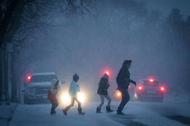 People dash across the street outside the Cathedral of St. Paul during a major winter storm, Wednesday, Dec. 23, 2020 in St. Paul, Minn. (Leila Navidi/Star Tribune via AP)