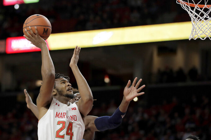 Maryland forward Donta Scott (24) goes up to shoot as Rhode Island forward Jermaine Harris, back, defends during the first half of an NCAA college basketball game, Saturday, Nov. 9, 2019, in College Park, Md. (AP Photo/Julio Cortez)