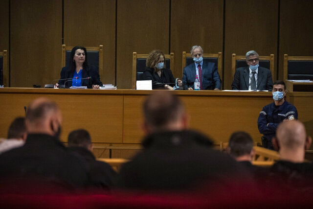 Presiding judge Maria Lepenioti , left, and members of the court listens during the Golden Dawn trial, in Athens, Monday, Oct. 19, 2020. A prosecutor has recommended all former lawmakers of Greece's extreme right Golden Dawn party who have been sentenced to prison for leading or participating in a criminal organization should be allowed to remain free pending appeal.(AP Photo/Petros Giannakouris)