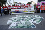 Fake bank notes showing images of U.S. President Donald Trump are displayed as protesters stage a rally to oppose the United States' demand for raising the defense costs for stationing U.S. troops in South Korea, near the U.S. embassy in Seoul, South Korea, Tuesday, Oct. 22, 2019. South Korean police have formally arrested four anti-American students who broke into the U.S. ambassador's residence in Seoul while protesting the Trump administration's demands for South Korea to pay more to help cover the costs of keeping U.S. troops. The sign reads