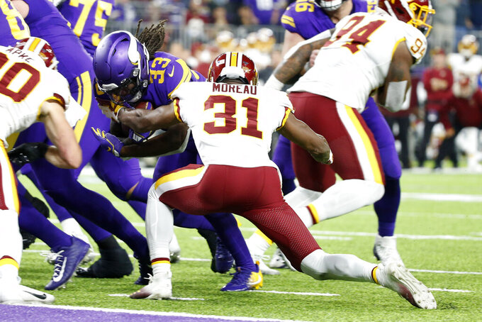 Minnesota Vikings running back Dalvin Cook (33) scores on a 4-yard touchdown run in front of Washington Redskins cornerback Fabian Moreau (31) during the first half of an NFL football game, Thursday, Oct. 24, 2019, in Minneapolis. (AP Photo/Bruce Kluckhohn)