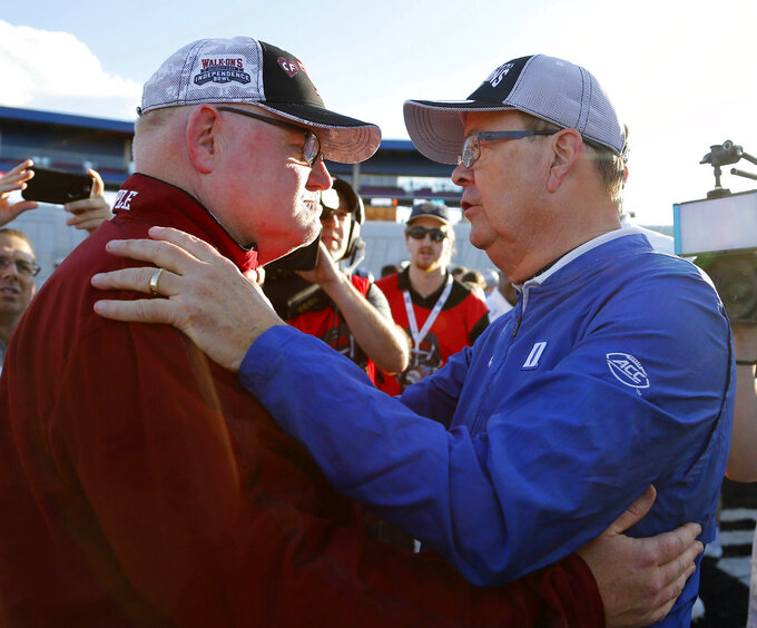 Duke head coach David Cutcliffe, right, confers with Temple interim head coach Ed Foley, left, following the Independence Bowl NCAA college football game in Shreveport, La., Thursday, Dec. 27, 2018. (AP Photo/Rogelio V. Solis)