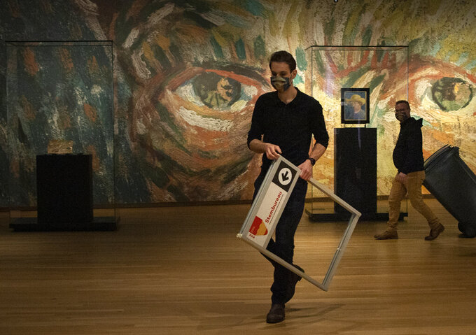 A ballot box is brought to a polling station inside the Van Gogh museum during a demonstration for the media in Amsterdam, Netherlands, Tuesday, March 16, 2021. Polling stations opened across the Netherlands early Monday and Tuesday in a general election that has been spread over three days to allow people to vote safely during the coronavirus pandemic. The Van Gogh museum is closed because of the pandemic. (AP Photo/Peter Dejong)