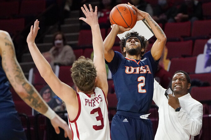 UTSA guard Jhivvan Jackson (2) shoots over Oklahoma guard Trey Phipps (3) during the first half of an NCAA college basketball game Thursday, Dec. 3, 2020, in Norman, Okla. (AP Photo/Sue Ogrocki)