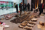 In this Jan. 9, 2020, photo provided by the Anti-Poaching Special Squad, police look at items seized from store suspected of trafficking wildlife in Guangde city in central China's Anhui Province. The outbreak of a new virus linked to a wildlife market in central China is prompting renewed calls for enforcement of laws against the trade in and consumption of exotic species. (Anti-Poaching Special Squad via AP)
