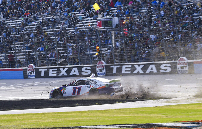 Denny Hamlin (11) wrecks into the grass on the front stretch during a NASCAR auto race at Texas Motor Speedway, Sunday, Nov. 3, 2019, in Fort Worth, Texas. (AP Photo/Randy Holt)