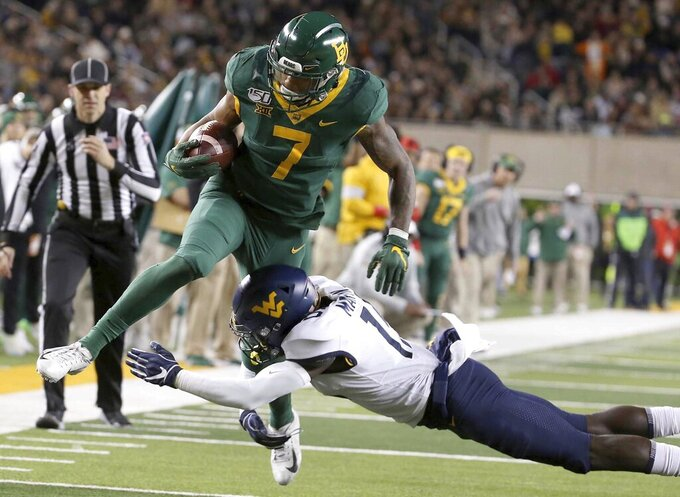 Baylor running back John Lovett (7) is tackled by West Virginia safety Kerry Martin Jr. (15) during the first half of an NCAA college football game in Waco, Texas, Thursday, Oct. 31, 2019. (AP Photo/Jerry Larson)