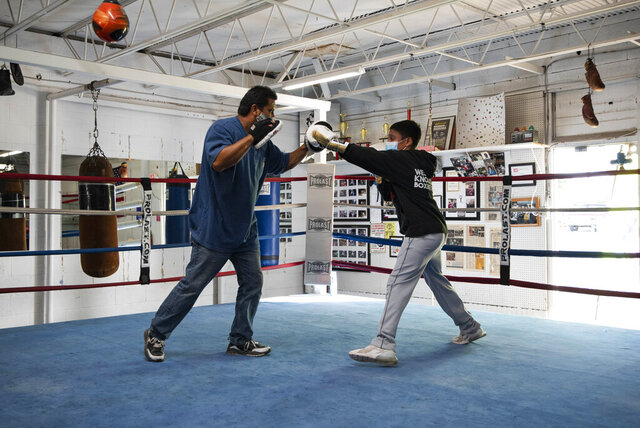 Coach Danny Chavez aids 14-year-old Estevan Rodriguez during boxing practice Tuesday, Aug. 4, 2020, at West Texas Knockout Boxing Club in Odessa, Texas. Both are wearing masks to abide by the boxing club's health and safety rules, to help prevent the spread of COVID-19. Tuesday was the club's first day open since late March. (Eli Hartman/Odessa American via AP)