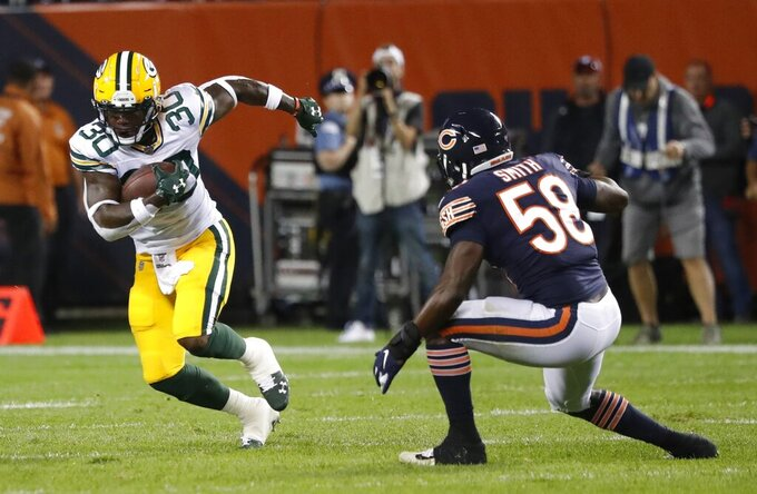Green Bay Packers' Jamaal Williams runs past Chicago Bears' Roquan Smith during the first half of an NFL football game Thursday, Sept. 5, 2019, in Chicago. (AP Photo/Charles Rex Arbogast)