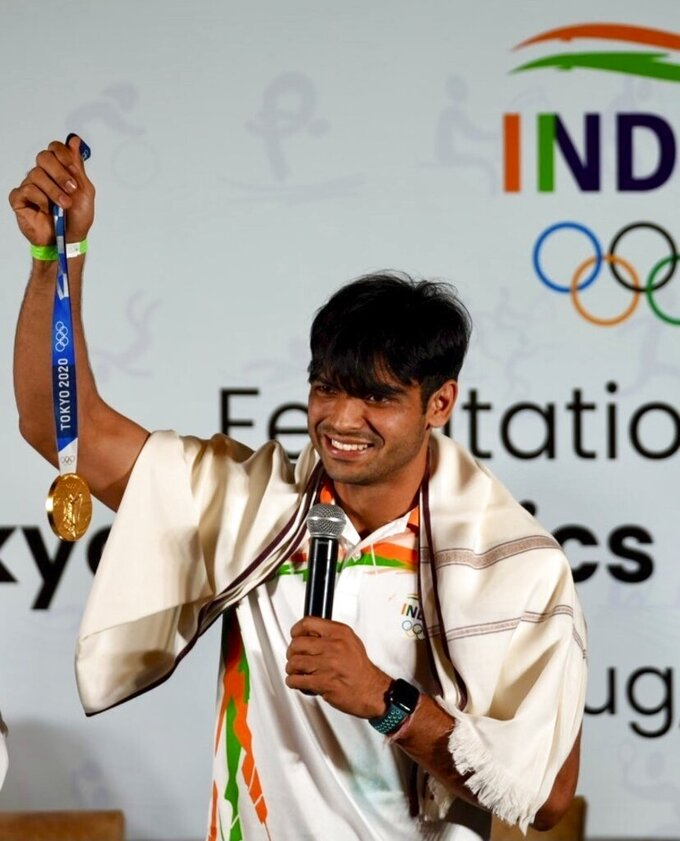 Olympic medallist Neeraj Chopra displays the gold medal he won in the men's javelin at the Tokyo Games during a felicitation function at Major Dhyan Chand National Stadium in New Delhi, India, Monday, Aug.9 2021. (AP Photo/Manish Swarup)