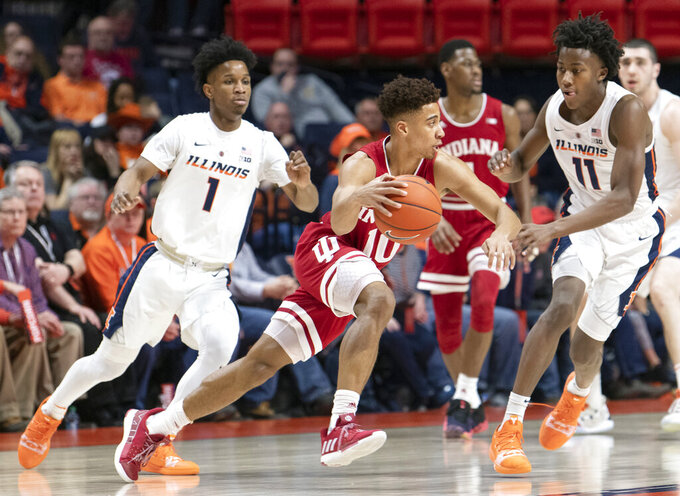 Indiana guard Rob Phinisee (10) moves the ball as Illinois guards Ayo Dosunmu (11) and Trent Frazier (1) defend during the first half of an NCAA college basketball game in Champaign, Ill., Thursday, March 7, 2019. (AP Photo/Stephen Haas)