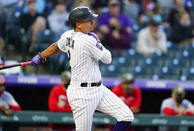 Colorado Rockies' Yonathan Daza connects for an RBI-single of Cincinnati Reds starting pitcher Wade Miley in the third inning of a baseball game Friday, May 14, 2021, in Denver. (AP Photo/David Zalubowski)