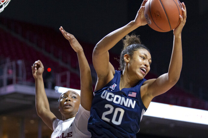 Connecticut forward Olivia Nelson-Ododa, right, grabs a rebound away from Temple forward Alexa Williamson, left, during the first half of an NCAA college basketball game Sunday, Nov. 17, 2019, in Philadelphia. (AP Photo/Laurence Kesterson)