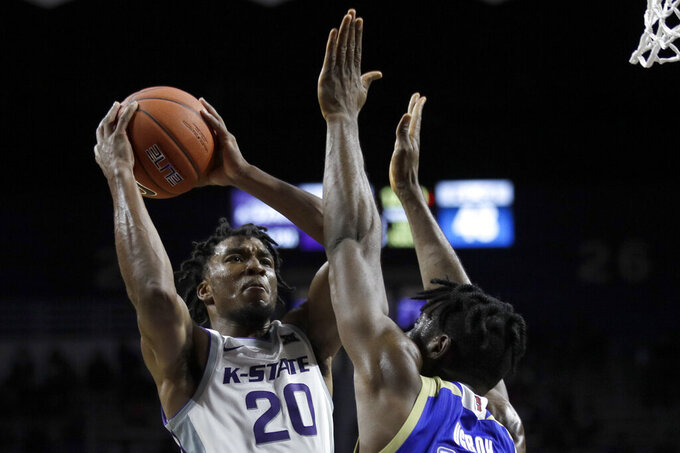 Kansas State forward Xavier Sneed (20) shoots over Tulsa center Emmanuel Ugboh (12) during the second half of an NCAA college basketball game in Manhattan, Kan., Sunday, Dec. 29, 2019. (AP Photo/Orlin Wagner)