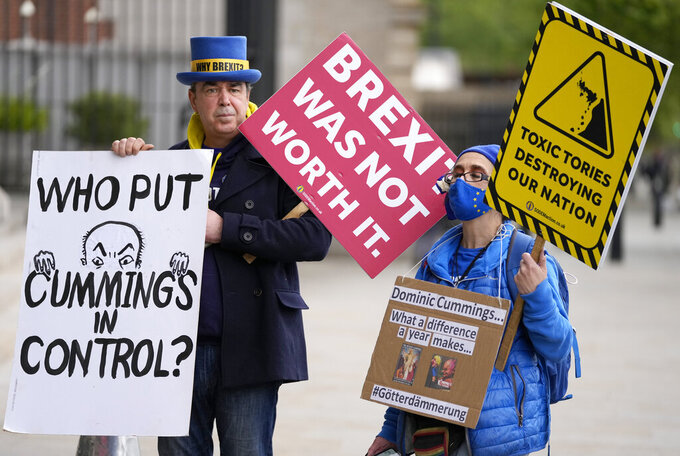 Protestors wait for Dominic Cummings, British Prime Minister Boris Johnson's most powerful and trusted aide up until last year, to arrive to attend a select committee hearing at Portcullis House in London, Wednesday, May 26, 2021. In recent days, Cummings has directed a torrent of criticism at Johnson's Conservative government in an ever-lengthening string of Twitter posts. On Wednesday, he plans to make the claims in person, testifying on live television to lawmakers investigating Britain's handling of COVID-19. (AP Photo/Frank Augstein)