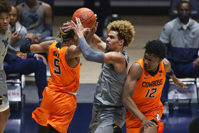 West Virginia forward Emmitt Matthews Jr. (11) is defended by Oklahoma State guard Rondel Walker (5) and forward Matthew-Alexander Moncrieffe (12) during the second half of an NCAA college basketball game Saturday, March 6, 2021, in Morgantown, W.Va. (AP Photo/Kathleen Batten)
