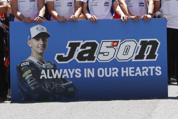 Teammates of 19 years-old Swiss pilot Jason Dupasquier pay a minute of silence in his memory prior to the start of the Motogp Grand Prix of Italy at the Mugello circuit, in Scarperia, Italy, Sunday, May 30, 2021. Dupasquier died Sunday after being hospitalized Saturday, at the Florence hospital following his crash during the qualifying practices of the Moto3. (AP Photo/Antonio Calanni)