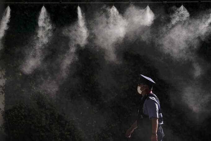 A cooling system sprays a mist over a police officer outside the main press center of the 2020 Summer Olympics, Friday, July 16, 2021, in Tokyo. (AP Photo/Jae C. Hong)