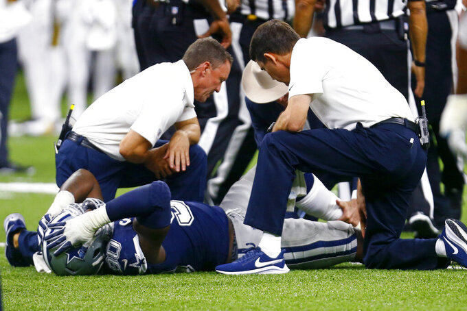 Dallas Cowboys defensive end Demarcus Lawrence (90) is tended to on the field after being injured in the second half of an NFL football game against the New Orleans Saints in New Orleans, Sunday, Sept. 29, 2019. The Saints won 12-10. (AP Photo/Butch Dill)