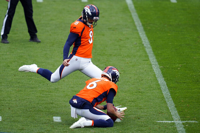 Denver Broncos kicker Brandon McManus kicks a field goal as Sam Martin holds during the first half of an NFL football game against the Tampa Bay Buccaneers, Sunday, Sept. 27, 2020, in Denver. (AP Photo/Jack Dempsey)