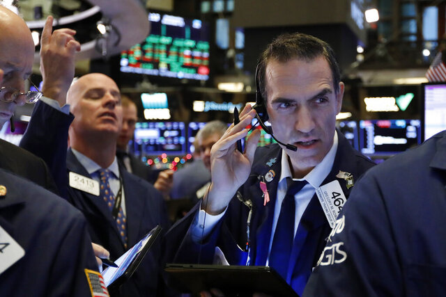 FILE - In this Dec. 11, 2019, file photo trader Gregory Rowe, right, works on the floor of the New York Stock Exchange. The U.S. stock market opens at 9:30 a.m. EST on Monday, Dec. 23. (AP Photo/Richard Drew, File)