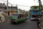 In this May 15, 2019 photo, a public bus drives through the San Miguel Teotongo neighborhood in the Iztapalapa borough of Mexico City. The paranoia about assaults and muggings has been amplified by the fact that so many of the robberies are now videotaped by surveillance cameras on public buses. (AP Photo/Rebecca Blackwell)