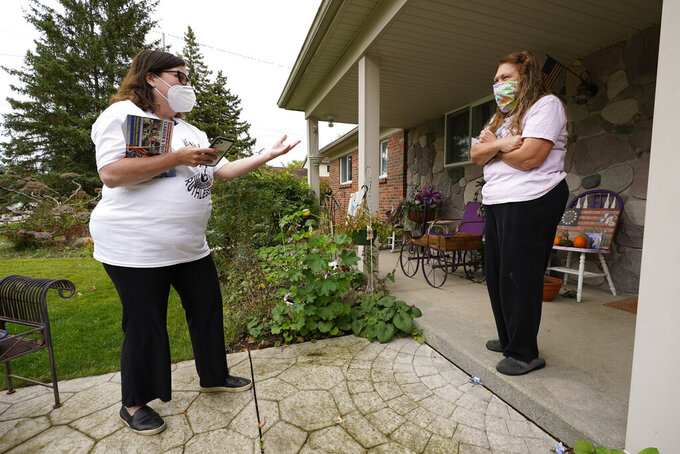 """FILE - In this Thursday, Oct. 15, 2020 file photo, Lori Goldman talks with a voter while canvassing in Troy, Mich. In suburban Michigan, a coalition of suburban women achieved what they set out to do _ help evict Donald Trump from the White House. But Goldman, who runs the group Fems for Dems, can't shake the sense that their mission now is more critical than it's ever been. """"We got rid of this blight, this cancer,"""" said Goldman, 61. """"We cut him out. But we know that cancer has spread, it's spread to soft tissue, other organs. And now we have to save the rest of the body."""" (AP Photo/Paul Sancya)"""