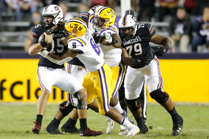 South Carolina quarterback Collin Hill (15) is brought down by LSU linebacker BJ Ojulari (8) during the first half of an NCAA college football game in Baton Rouge, La., Saturday, Oct. 24, 2020. (AP Photo/Brett Duke)