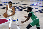 Milwaukee Bucks' Giannis Antetokounmpo (34) looks to pass around Boston Celtics' Jaylen Brown (7) during the first half of an NBA basketball game Friday, July 31, 2020, in Lake Buena Vista, Fla. (AP Photo/Ashley Landis, Pool)