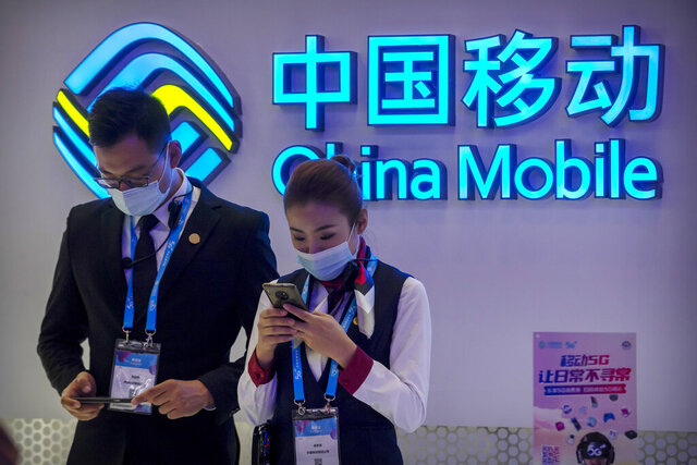 FILE - In this Oct. 14, 2020 file photo, staff members wearing face masks to protect against the spread of the coronavirus use their smartphones at a display from Chinese telecommunications firm China Mobile at the PT Expo in Beijing.  The New York Stock Exchange is going ahead with plans to delist shares of three Chinese state-owned phone carriers under an executive order from President Donald Trump.  The exchange said trading in the three companies, China Telecom Corp. Ltd., China Mobile Ltd. and China Unicom Hong Kong Ltd., will be suspended after the markets close on Jan. 11, 2021.   (AP Photo/Mark Schiefelbein, File)