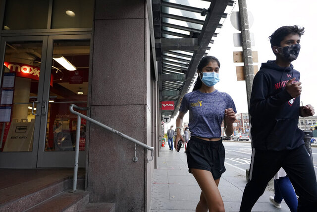 Runners wear masks out of concern for the coronavirus while jogging along a sidewalk, Tuesday, Oct. 27, 2020, in Boston. (AP Photo/Steven Senne)
