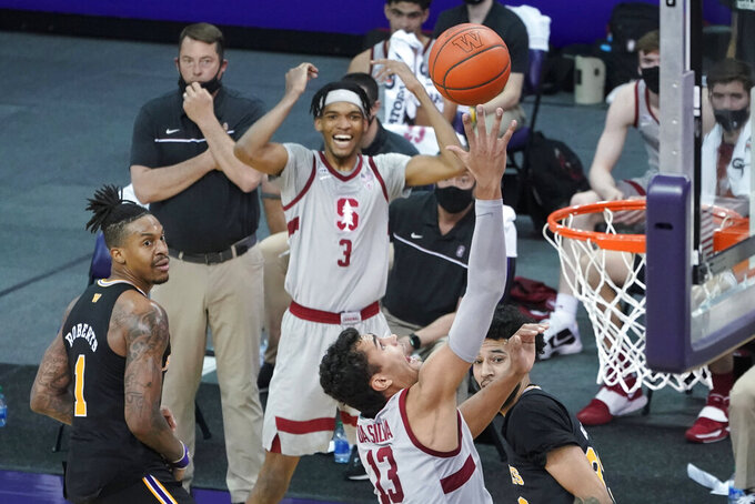 Stanford forward Oscar da Silva (13) shoots as Ziaire Williams (3) reacts from the bench and Washington forward Nate Roberts, left, looks on, during the second half of an NCAA college basketball game Thursday, Feb. 18, 2021, in Seattle. (AP Photo/Ted S. Warren)