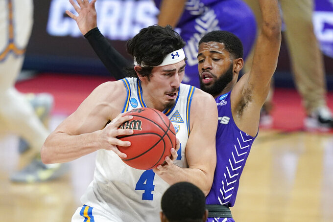 UCLA's Jaime Jaquez Jr. (4) drives against Abilene Christian's Reggie Miller during the first half of a college basketball game in the second round of the NCAA tournament at Bankers Life Fieldhouse in Indianapolis Monday, March 22, 2021. (AP Photo/Mark Humphrey)