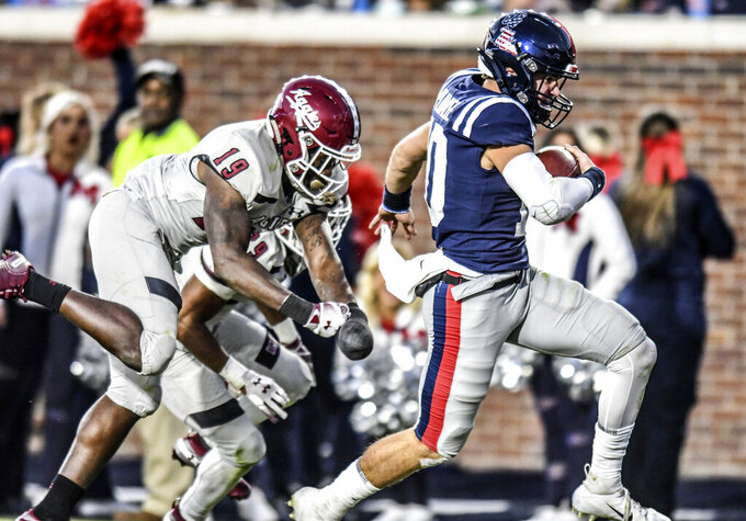Mississippi quarterback John Rhys Plumlee (10) runs past New Mexico State defensive back Austin Perkins (19) to score during an NCAA college football game in Oxford, Miss., Saturday, Nov. 9, 2019. (Bruce Newman/The Oxford Eagle via AP)
