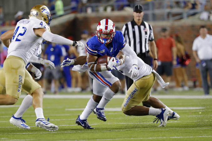 SMU running back Xavier Jones, center, rushes the ball while Tulsa linebacker Cooper Edminston (42) looks to tackle during the first half of an NCAA college football game, Saturday, Oct. 5, 2019, in Dallas, Texas. (AP Photo/Roger Steinman)