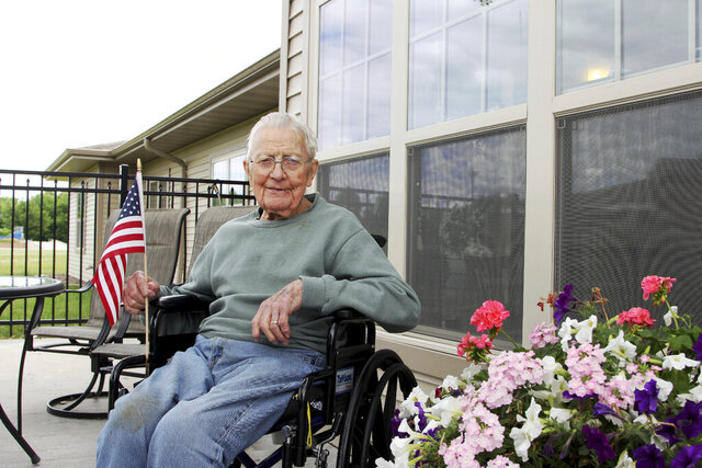 Beloit resident Bob Jackson holds an American flag while enjoying the nice weather on the Willowick Assisted Living in Beloit on June 23, 2020. Jackson, 97, served in the U.S. Navy during World War II and was present for the Japanese surrender on Sept. 2, 1945 in Tokyo Bay aboard the U.S.S. Missouri.  (Austin Montgomery/The Beloit Daily News via AP)