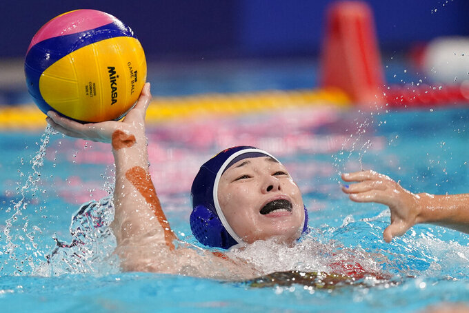 China's Xinyan Wang passes the ball away as she backs away from a defender during a preliminary round women's water polo match against the United States at the 2020 Summer Olympics, Monday, July 26, 2021, in Tokyo, Japan. (AP Photo/Mark Humphrey)