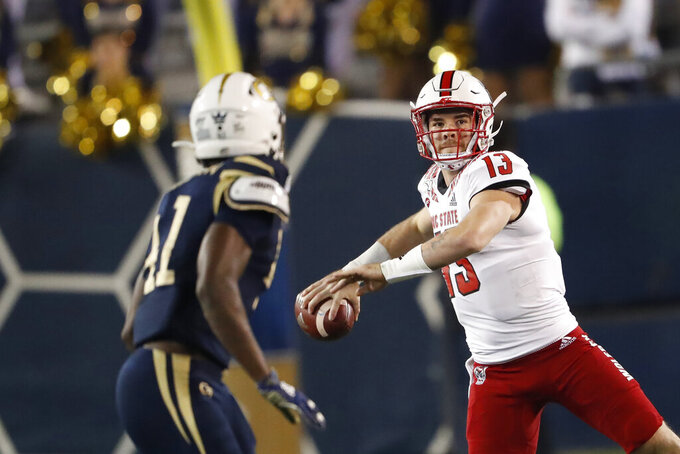 North Carolina State quarterback Devin Leary (13) looks for a receiver as Georgia Tech defensive lineman Jaquan Henderson (41) watches during the first half of an NCAA college football game Thursday, Nov. 21, 2019, in Atlanta. (AP Photo/John Bazemore)
