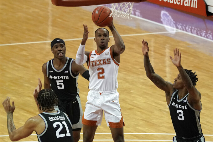 Texas' Matt Coleman III (2) shoots against Kansas State players Rudi Williams (5), DaJuan Gordon (3) and Davion Bradford (21) during the first half of an NCAA college basketball game in Austin, Texas, Saturday, Jan. 16, 2021. (AP Photo/Chuck Burton)